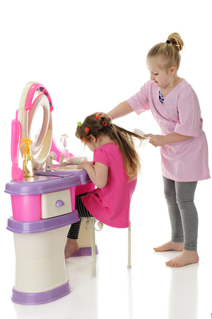Two sisters playing beauty salon. The older one is holding her sisters head with one hand while pulling the brush through tangled hair with the other one. On a white background.