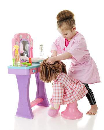 An adorable preschool hair stylist trying to get the tangles out of her dolls yarn hair.  On a white background.