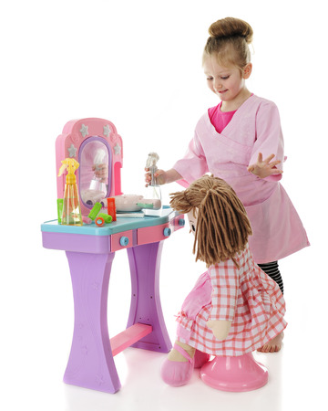 smock: An adorable preschool hair sytlist pleased with the hairdo shes given her doll.  On a white background. Stock Photo