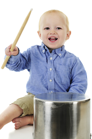 upraised: An adorable toddler sitting with and upraised drumbstick, ready to play the crock pot before him.