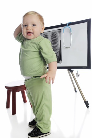 An adorable toddler playing x-ray technician in front of a chest x-ray on an easle.  On a white background.