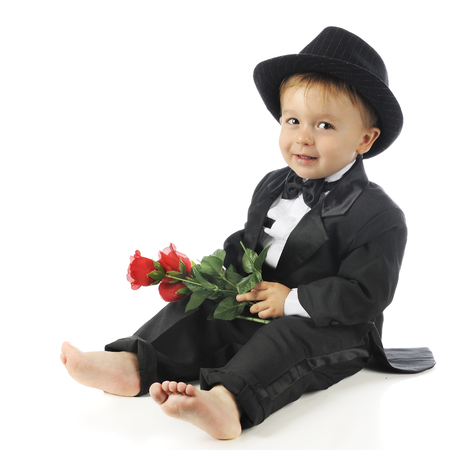 Ad adorable preschool sitting barefoot  in his tuxedo and fedora . He's looking at the camera while holding a small bouquet of roses.  On a white background.