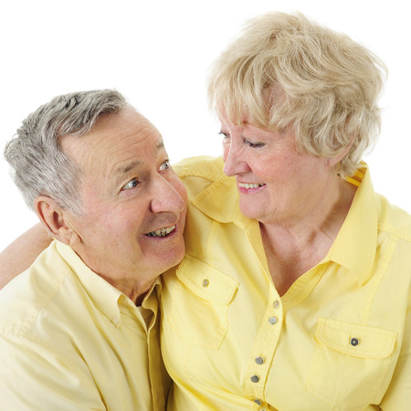 A senior man looking adoringly into his wife's eyes.  On a white background. Imagens