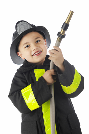 Close-up image of a young elementary fireman  looking at the viewerwhile holding a hose, pointed and ready for the spray.  On a white background. Фото со стока