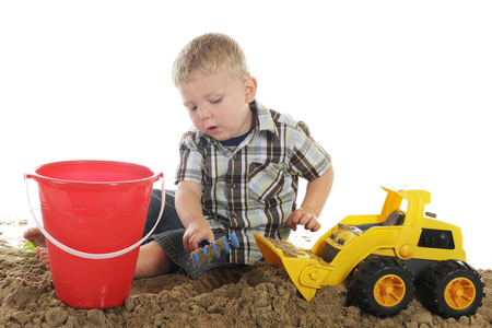 plastic scoop: A young preschooler using his truck and hand rake to scoop up sand for his pail.  On a white background.