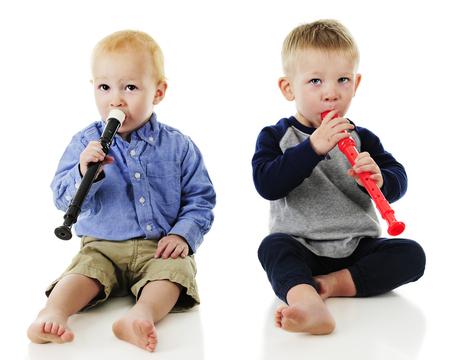 Dos muchachos del niño adorable que juega lado a lado grabadoras. Sobre un fondo blanco.