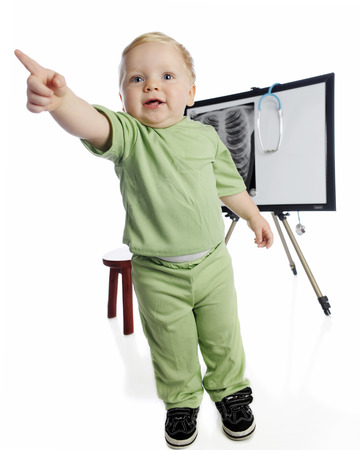 An adorable toddler boy playing x-ray technician. Hes standing, pointing away from the xpray on an easel behind him.  On a white background.