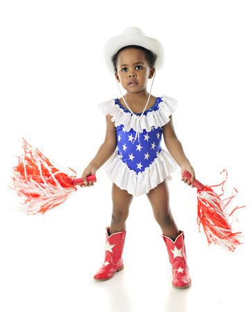 An adorable African American patriot shaking pom-poms whiel dressed in a star studded, red, white and blue western outfit.  On a white background.