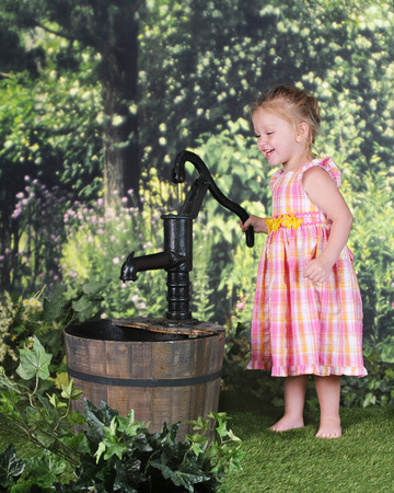 An adorable 2 year old happily playing with an old-time water pump on a warm summer day.