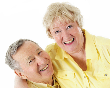 A laughing senior couple, both dressed in sunny yellow shirts.  On a white background.