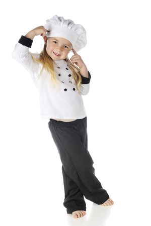 An adorable preschooler standing in her chefs outfit with fingers pointing to her head while smiling at the viewer.  On a white background. Stock Photo