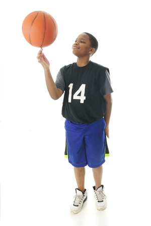 A handsome preteen boy proudly spinning his basketball on his index finger.  Motion blur on the ball.  On a white background. Imagens