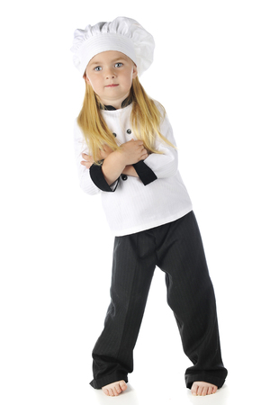 A pretty preschooler barefoot in her chef outfit, looking at the viewer.  On a white background.  Imagens