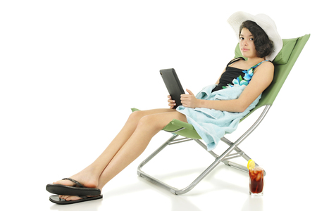 An attractive young teen chilling out on a beach chair in her beach outfit.  Shes looking up at the viewer from her ipad and has a tall glass of iced tea by her side.  On white background. Stock Photo