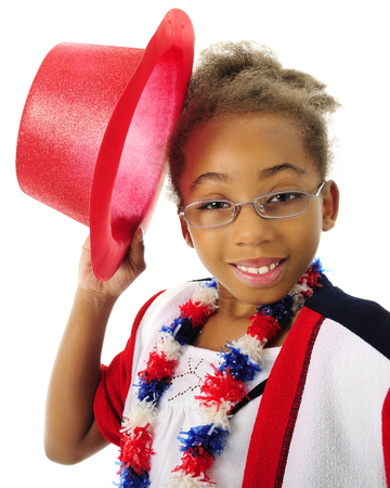 Close-up image of an elementary African American girl happily tipping her red top hat.  On a white background.