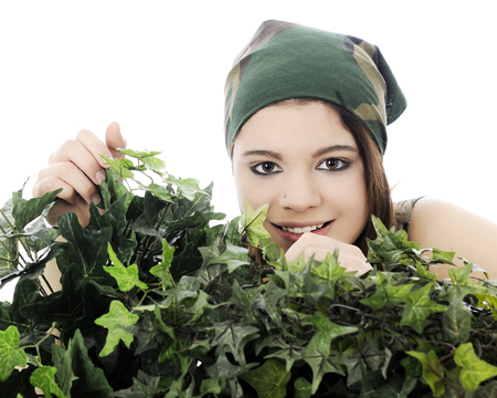 A beautiful teen girl in camouflage, smiling behind thick foliate.  On a white background.