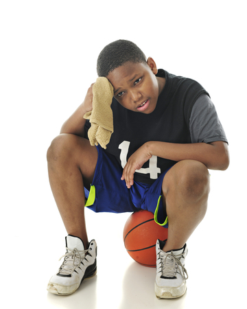 A preteen athlete looking tired and wiping his brow while resting on his basketball.  On a white background. Imagens - 76820110