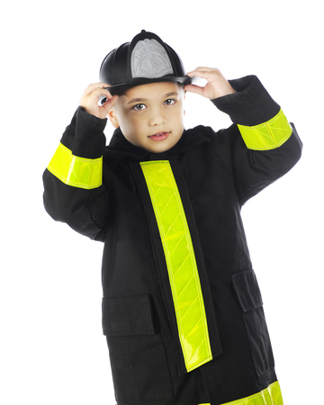 A young elementary boy putting on his chiefs hat while wearing his firemans coat.  On a white background. Stock Photo