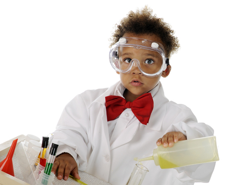 An adorable preschool chemist in safety goggles and lab coat mising chemicals on his science table.  On a white background.