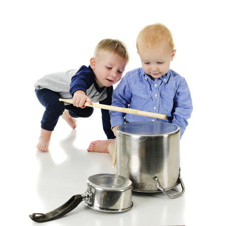 One toddler teaching another toddler how to bang on a pot with a drumstick.  On a white background.