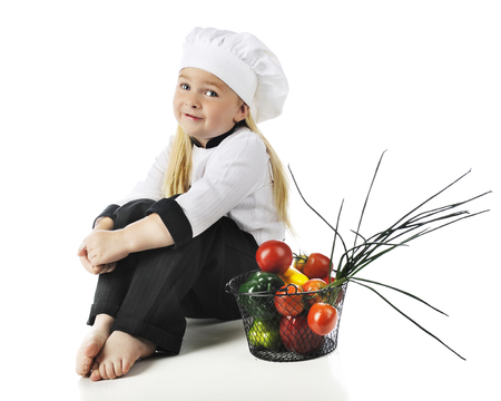 An adorable preschool chef happily sittting by a basket of fresh vegetables.  On a white background.