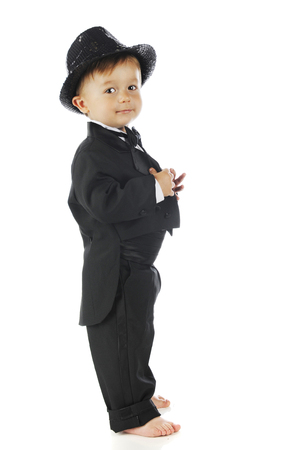 An adorable preschooler looking at the viewer as he stands barefoot in his tuxedo and top hat.  On a white background.
