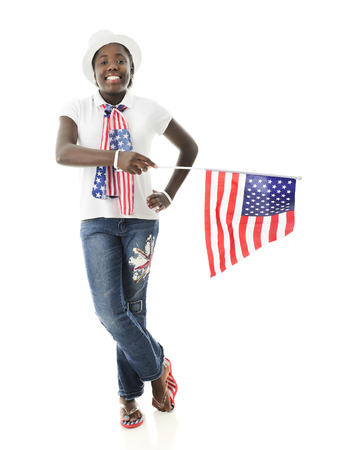 An attractive preteen girl proudly wearing her stars and stripes while holding the American flag.  On a white background. Imagens - 76820119