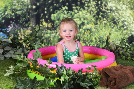An adorabel 2 year old smiling at the viewer as she sits pretty in her kiddie pool on a sunny summer day. Imagens