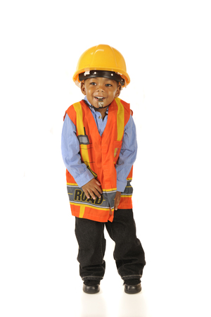 An adorable preschooler happily blowing a whistle while dressed in his road crew gear.  Isolated on white. Imagens
