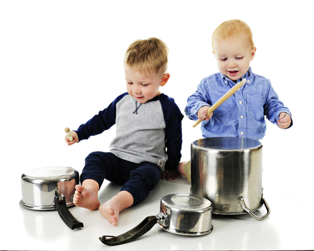Two adorable toddler cousins beating kitchen pots and pans with sticks.  motion blur on drum stick.  On a white background.