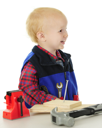 Profile of a laughing todder playing handyman. He stands behind a table of toy tools and real wooden blocks with a nail in them.  On a white background. Imagens - 80866582