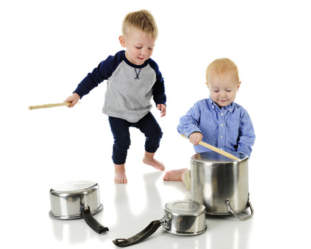 arrodillarse: Two adorable toddlers playing drums on kitchen pots and pans.  One is kneeling, playing a crock pot, the other is walking up behing him with the drumstick ready for a major whack.  On a white background. Foto de archivo