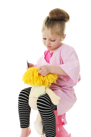 An adorable preschool girl in her hairdresser smock, combing her dolls blond yarn hair.  On a white background.