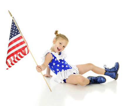An adorable preschooler sitting on the ground in her patriot outfit, happily showing off her American flag.  On a white background. Imagens