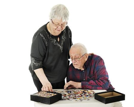 A senior adult couple working on a jigsaw puzzle together.  On a white background. Imagens