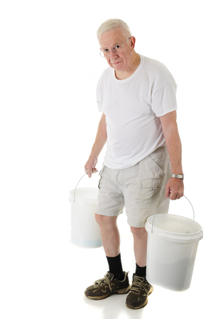 A senior man hunched and looking at the viewer as he carries two white buckets.  On a white background. photo