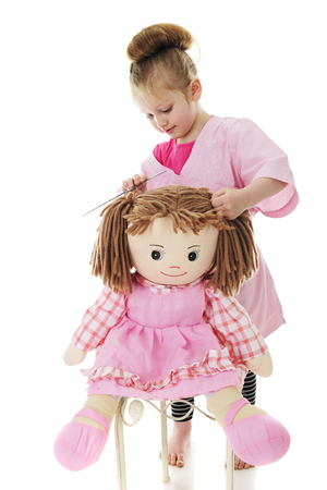 An adorable preschooler playing hair stylist with her doll.  On a white background. Imagens - 80894618