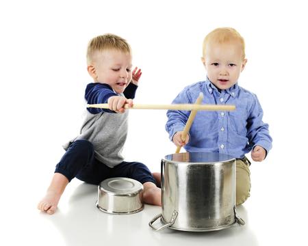 """Dos niños adorables jugando """"tambores"""" junto con los palillos y las macetas y las cacerolas al revés. Sobre un fondo blanco."""