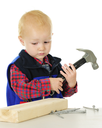 An adorable toddler sadly looking at a block of wood and nails with a toy hammer in his hands.  On a white background. Imagens