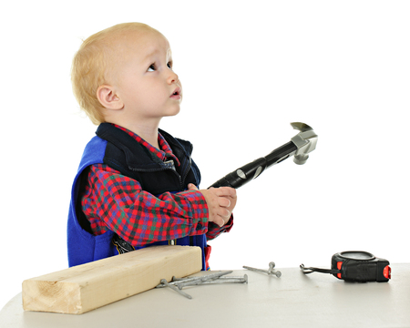 An adorable toddler with a hammer in hand, a block of wood and nails to his side. Hes looking as if asking a parent if hes allowed to play with these.  On a white background. Banco de Imagens