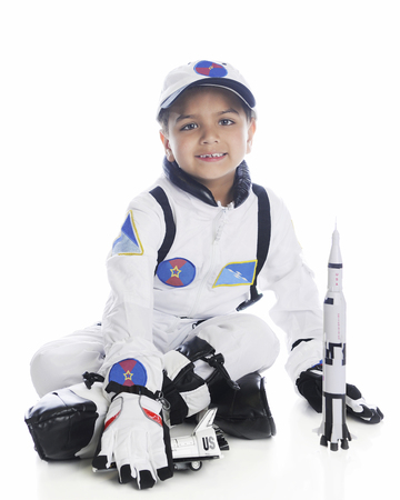 A young elementary boy playing astronaut. Hes in his space suit by a toy rocket.  On a white background.