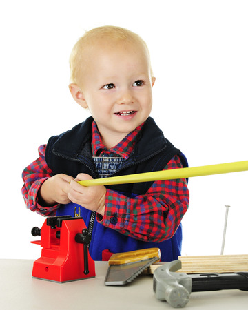 Ad adorable toddler playing tool man.  He's holding one end of a tape measurer, while the other is being held out of the viewer's sight.  On a white backgroundl. Imagens - 80853852