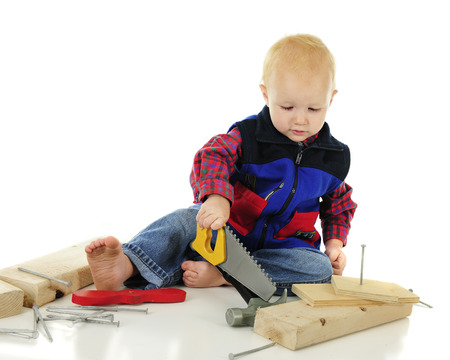 An adorable toddler playing tool-man trying to saw hile holding the tool upside-down. Nails, a hammer and blacks of wood surround him.