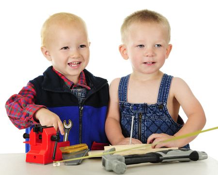 Two adorable toddlers standing at a tool bench with several toy tools, wooden boards and a large nail.  On a white background. Imagens - 80863807