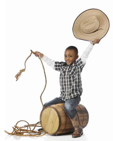 A happy young boy smiling at the viewer as he ridies an old barrel as he plays cowboy.  On a white background.