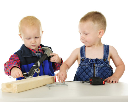 Two toddler boys pretending to be handyman with their toy hammer, long nails, a blocks of wood and tape measurer.  On a white background. Banco de Imagens
