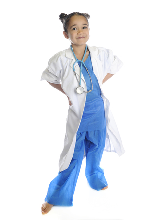 A happy young elementary girl standing barefoot in her scrubs and lab coat.  On a white background.