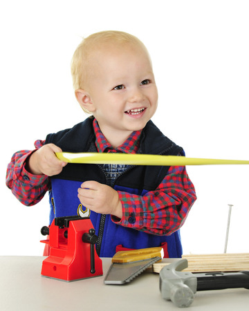 An adorable toddler, delightedly holding one end of a tape measurer. Other tools are on the tabletop before him.  On a white background.