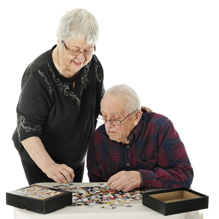 A senior adult man watching his wife as she chooses a piece for his jigsaw puzzle.  On a white background. Imagens - 115278944
