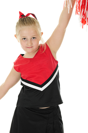 An adorable elementary cheerleader in uniform, looking at the viewer as she holds her pom pom high.  On a white background.